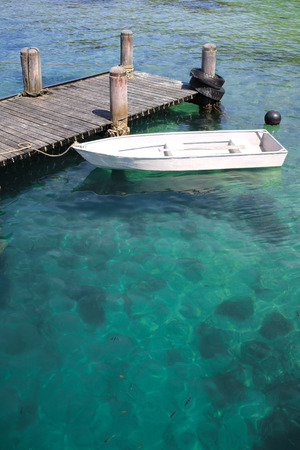 dalmatia: view of small boat park at wood jetty with crystal clear asian water Stock Photo