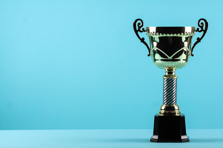 award background: gold award winning trophy in pastel blue background