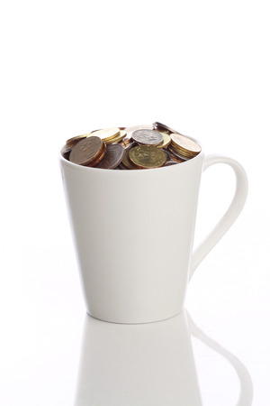 white cup full of malaysian coins isolated in white