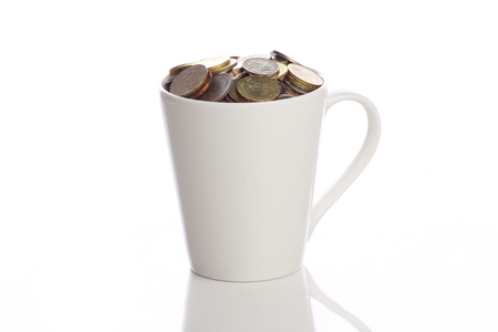 kopek: white cup full of malaysian coins isolated in white