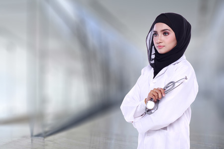 muslimah doctor holding a stethoscope isolated on blur background 版權商用圖片