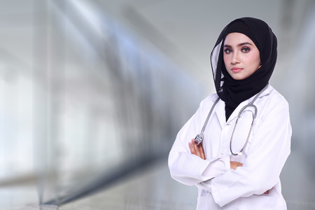muslimah: muslimah doctor holding a stethoscope isolated in blur background