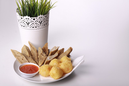 keropok lekor with fried yam served with chili sauce isolated on wooden background