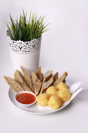 keropok: keropok lekor with fried yam served with chili sauce isoalted on wooden background Stock Photo