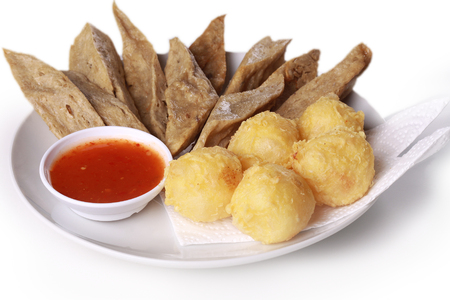 keropok: keropok lekor with fried yam served with chili sauce isolated on wooden background