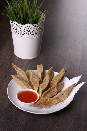 keropok lekor served with chili sauce isolated on wooden background