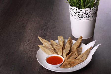 keropok: keropok lekor served with chili sauce isolated on wooden background