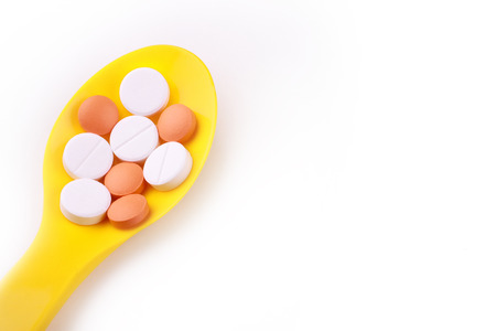 yellow spoon and pills isolated on white background