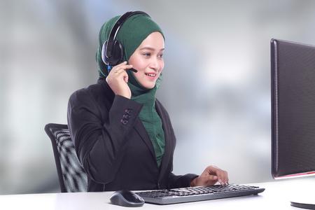 Operador de línea telefónica joven mujeres musulmanas hablando sobre fondo borroso Foto de archivo - 66141420