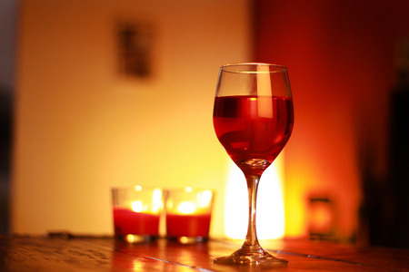 red wine in glass with a living room background and and ambient light Stock Photo
