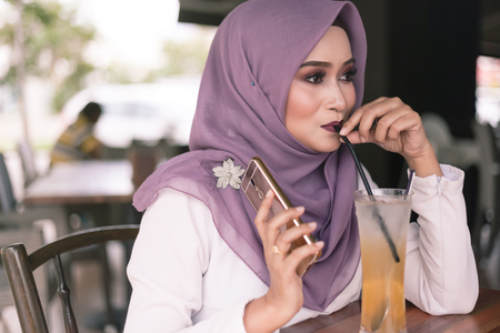 young woman have a drink at cafe while holding a smartphone