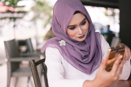 beautiful young woman doing a bussines with her smartphone at cafe Stock Photo