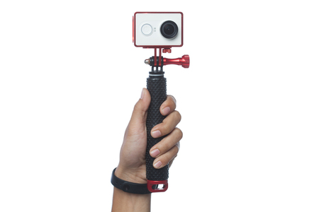 a hand is holding a action camera with monopod stick isolated with white background Stock Photo