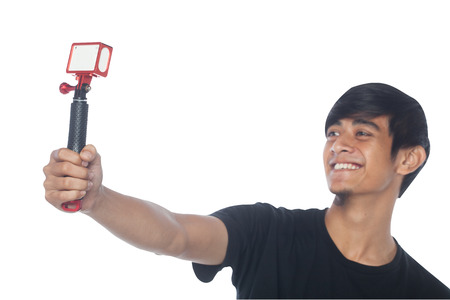 A man is holding action camera with monopod while taking selfie, focus on action camera. Stock Photo
