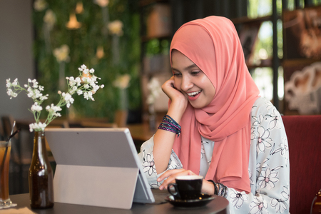 Happy young woman using tablet computer in a cafe while enjoy the coffee.