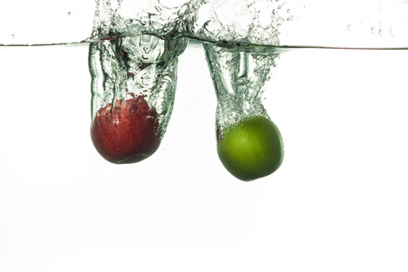 Fresh two apples falling into water with splashes