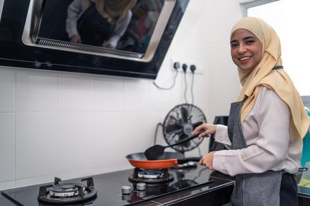 asiatische schöne Frau, die an der Küche kocht