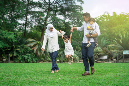 malay family having quality time in a park with morning mood