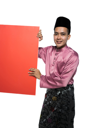 asian man with malay traditional attire holding a promotional card Imagens