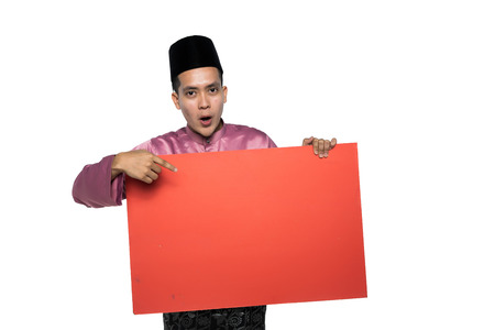 asian man with malay traditional attire holding a promotional card 版權商用圖片