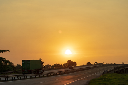 big lorry trailer transportation in a highway sunset view Archivio Fotografico