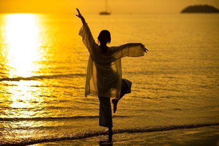 asian woman do a yoga on sea sunset