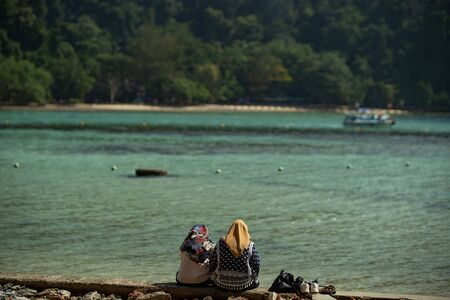 two asian muslim woman setting at the jetty and looking at the sea Фото со стока