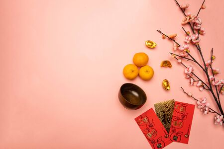flat lay of mandarin orange and gold packet with chinese character
