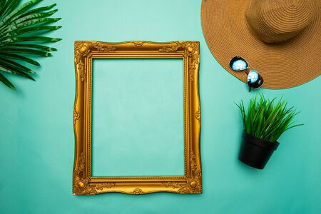 flat lay of brown beach hat and frame on turquoise background
