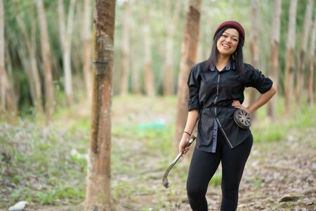 Female rubber tappers in the rubber tree row. Smiling look at the camera Stock Photo