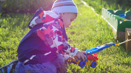a child plays with a toy car on the lawn. Fun and games outdoors Stock Photo