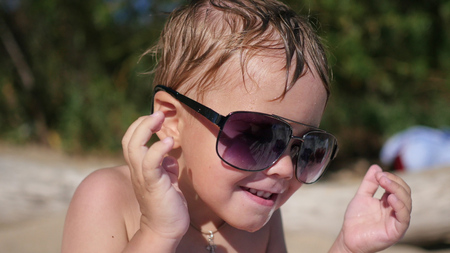 The child tries to wear sunglasses. The beach, a Sunny hot day Stock Photo