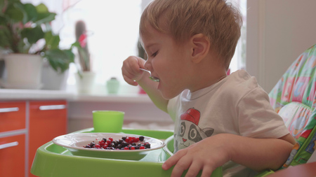 The child sits at the table and eats a spoonful of fresh berries. Useful and healthy food 版權商用圖片