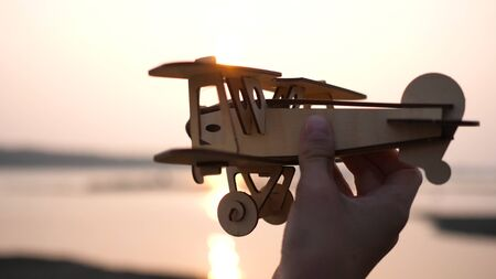 the child holds a plane in his hand against the setting sun, simulates the flight. Close up