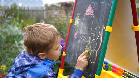 Young artist draws on the Board. A boy in the open air among the flowers and greenery draws childrens pictures with chalk on the Board. Stock Photo