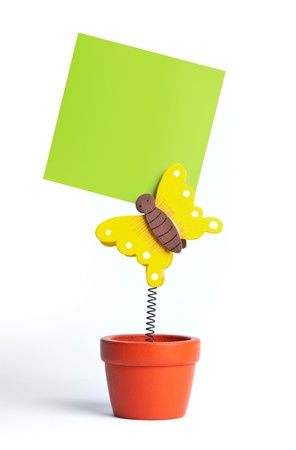 peddle: Notepaper attached by a butterfly toy in a flowerpot Stock Photo
