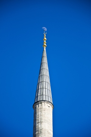 Image of a minaret top on bright blue sky background with the moon above photo