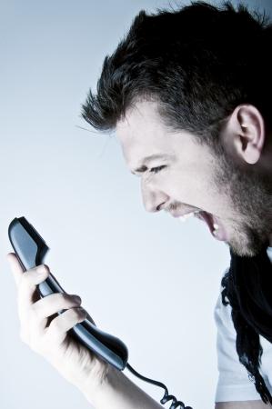 Angry young man schreeuwen op de bedrade telefoon