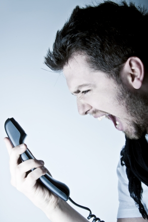 pissed: Angry young man shouting on the wired telephone