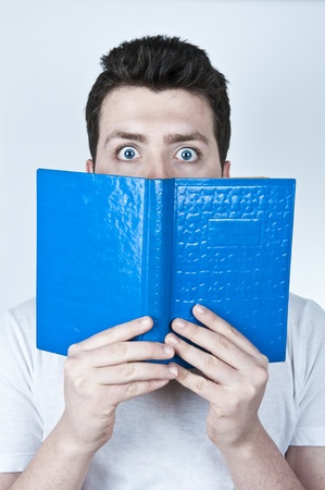 Isolated image of a young man afraid reading a book with blue hard cover Stock Photo - 9069399
