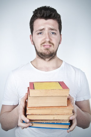 Isolated image of a sad student holding many books Stock Photo - 9069385