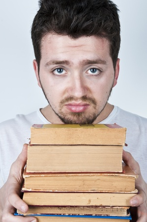 Young man holding a stack of old books looking bored and unhappy Stock Photo - 9069386