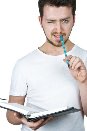 Young student winking and taking his notes on organizer wtih turquoise pen, the same color with his eyes Stock Photo - 9069381