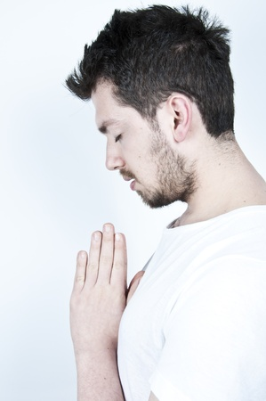 Praying young bearded man on white background Stock Photo - 9069382