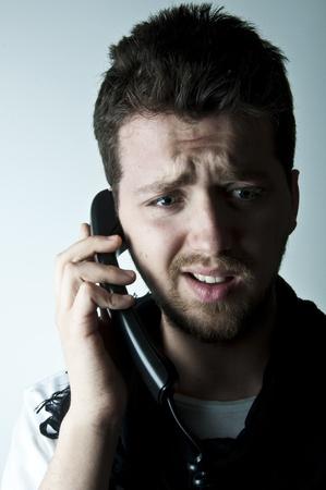 business skeptical: Joven hablando por un tel�fono con cable Foto de archivo
