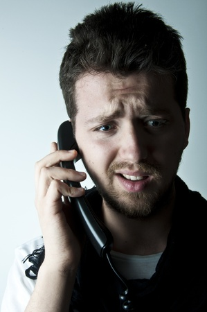 upset man: Young man talking on a wired phone