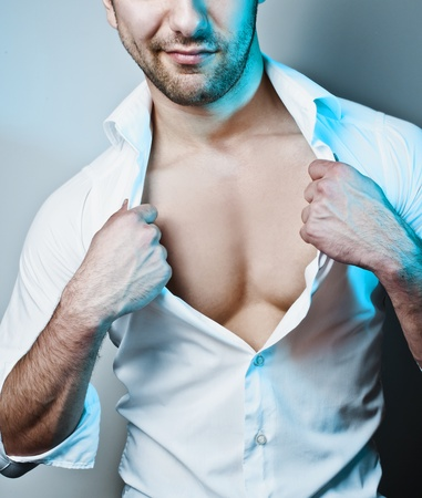 Studio shot of a young sexy man unbuttoning his white shirt under blue spotlight photo