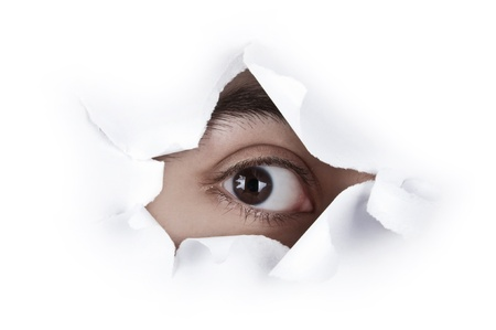 Isolated image of single brown eye looking through a hole on white paper