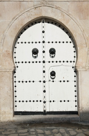 Image of traditional white Tunisian door with metal ornaments photo