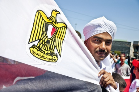 egypt revolution: An Egyptian man in traditional dress holding the Egyptian Flag in a march held in Taksim, Istanbul, Turkey
